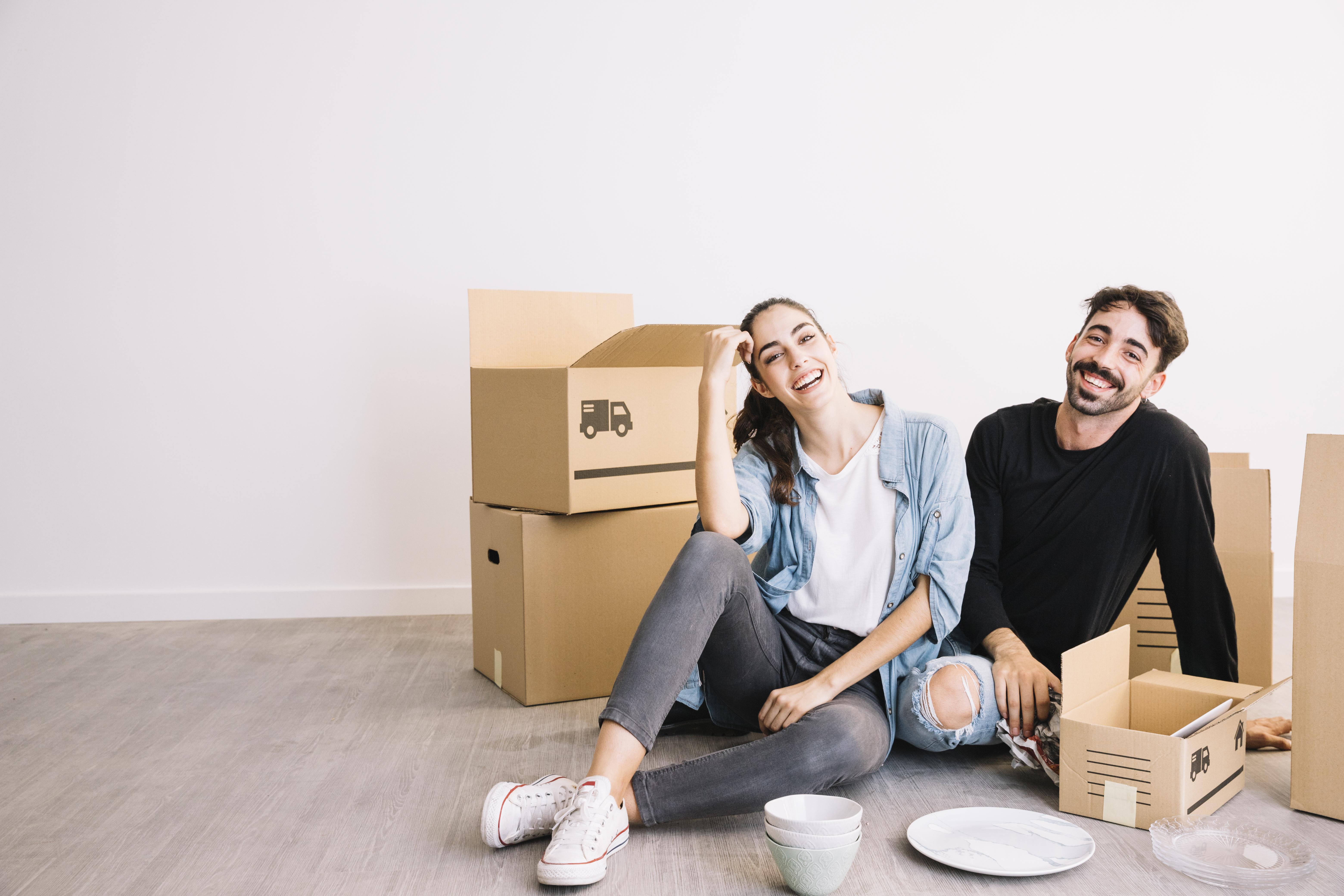 Una pareja sentada con cajas de mudanza con seguro de inquilinos
